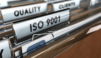 Close up on a file tab with the word ISO 9001 focus on the main text and blur effect. Concept image for illustration of Quality Standards